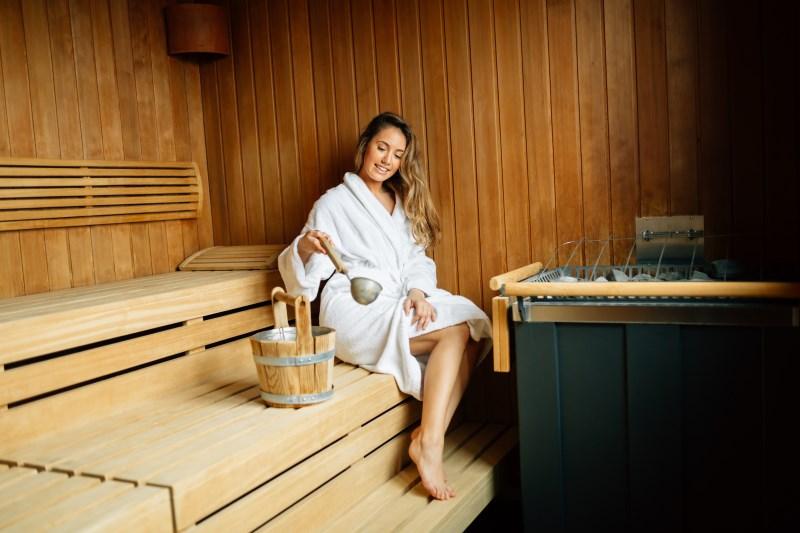Beautiful woman in finnish sauna caring about health and skin