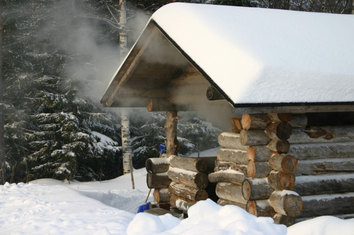 Finnish smoke sauna in the woods with steam coming out of it