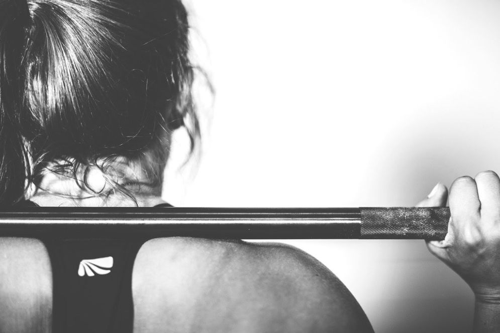 Woman working out with a barbell: How to Stick to a Workout Routine