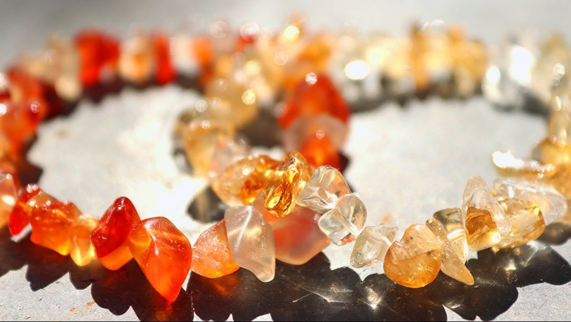 Red and orange crystal bracelets with white gemstones