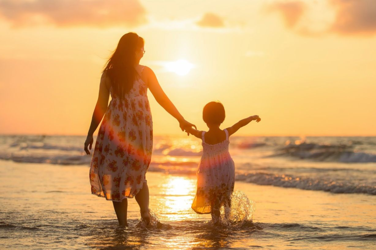 mother and daughter walking on a beach; find the best Mother's Day gift with HealthyLine